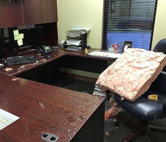 Water damaged office with a wet office, chair, and desktop items