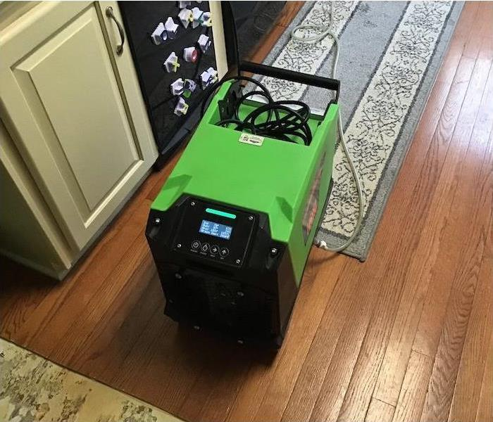 dehumidifier running in kitchen with water damage