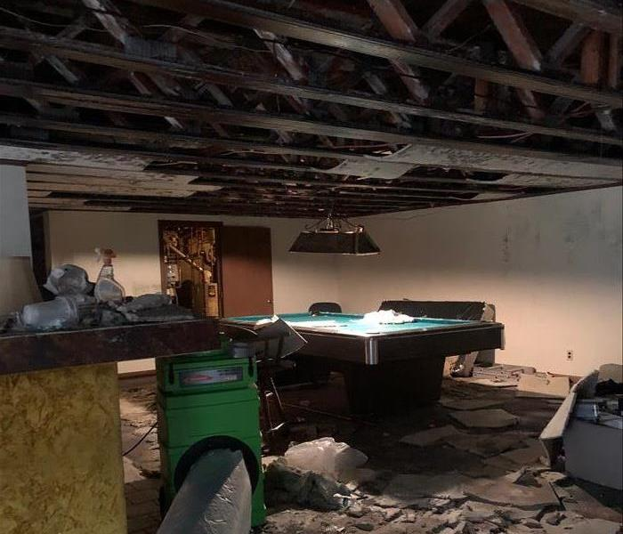 Charred ceiling showing rafters, debris on the floor by the pool table, and the green air scrubber with a duct at work