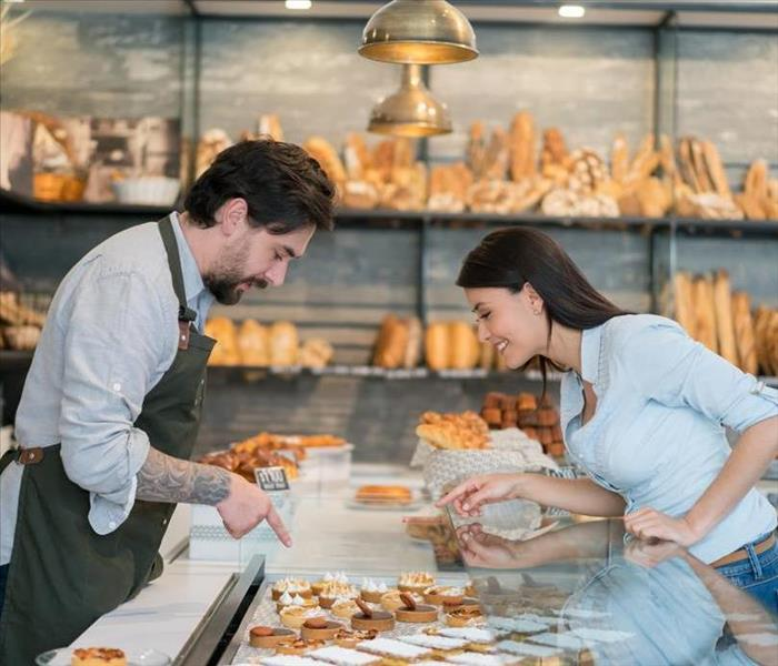 A man and a woman looking at backed goods in a bakery.