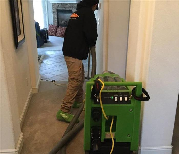SERVPRO team member extracting water from a hallway carpet